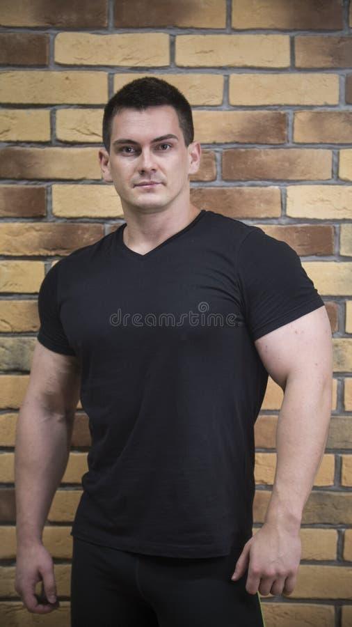 Atleta atrativo e muscular - retrato do desportista considerável novo perto da parede de tijolo fotografia de stock royalty free