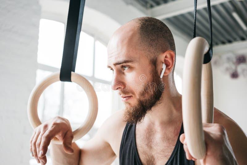 Atleta barbudo fuerte con el auricular inalámbrico que celebra los anillos crosstraining en el pasillo del crossfit foto de archivo libre de regalías