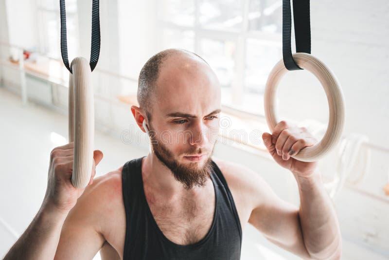 Atleta barbudo fuerte con el auricular inalámbrico que celebra los anillos crosstraining en el pasillo del crossfit imágenes de archivo libres de regalías