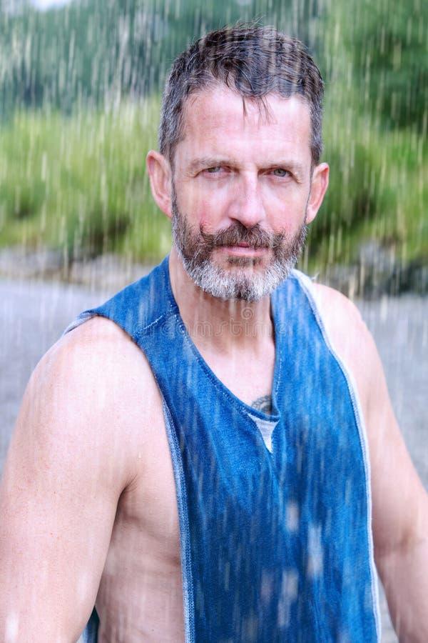 Atleta barbuto bello che sta all'aperto nella pioggia fotografia stock libera da diritti