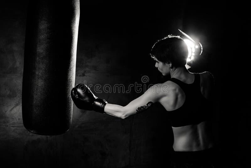 Atleta boksera kobieta uderza pięścią uderza pięścią torbę obraz royalty free