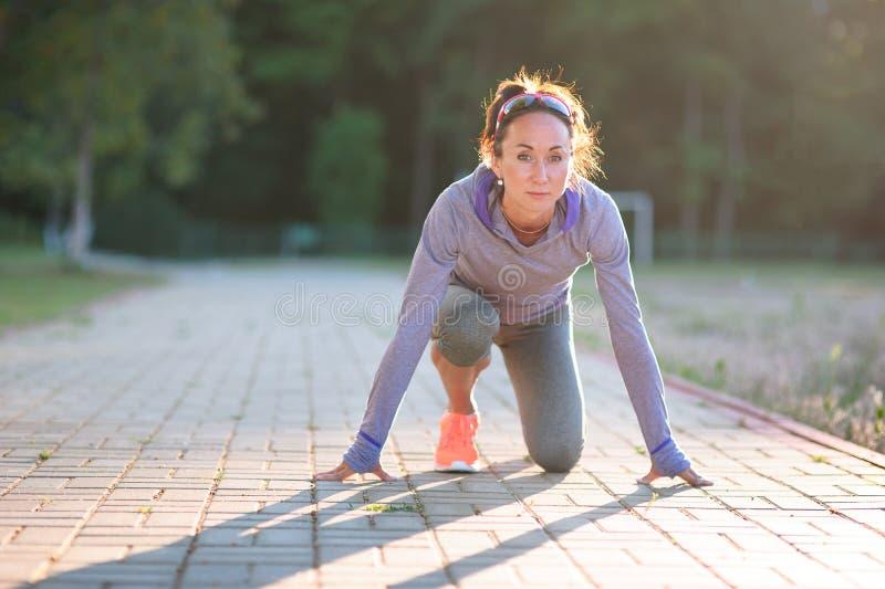 Atleta in buona salute della giovane donna di misura attraente che inizia correre alla t immagine stock