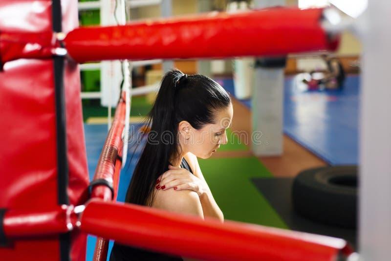 Atleta cansado de la muchacha que se sienta en el ring de boxeo mujer hermosa que se detiene por el hombro foto de archivo libre de regalías