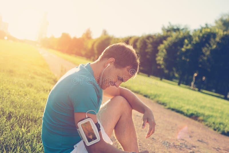 Atleta cansado feliz que senta-se no parque no por do sol imagem de stock