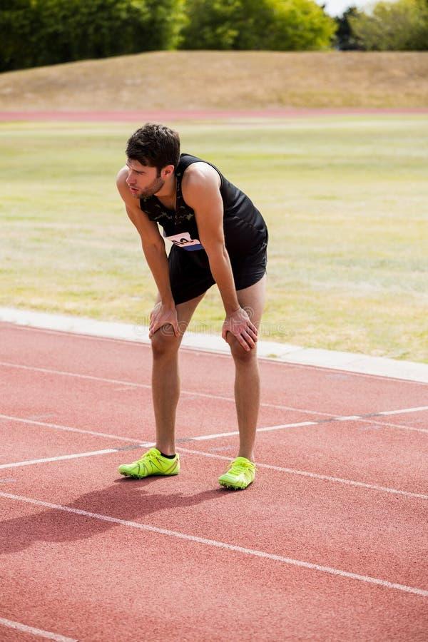 Atleta cansado que se coloca en pista corriente imagen de archivo