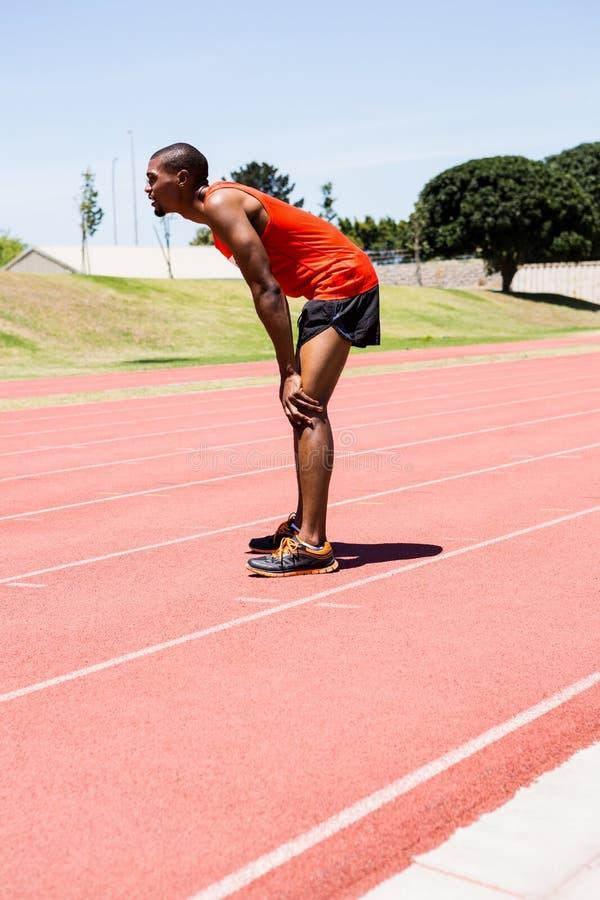 Atleta cansado que se coloca en pista corriente fotografía de archivo libre de regalías