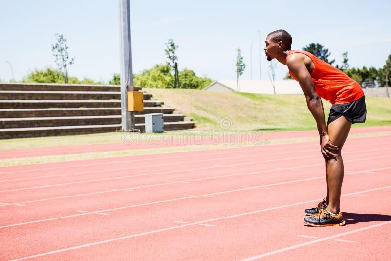 Atleta cansado que se coloca en pista corriente foto de archivo