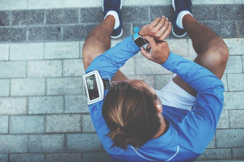 Atleta che controlla i risultati sugli orologi astuti, sedentesi sulla via dopo la sessione di allenamento e riposante, bracciale immagini stock