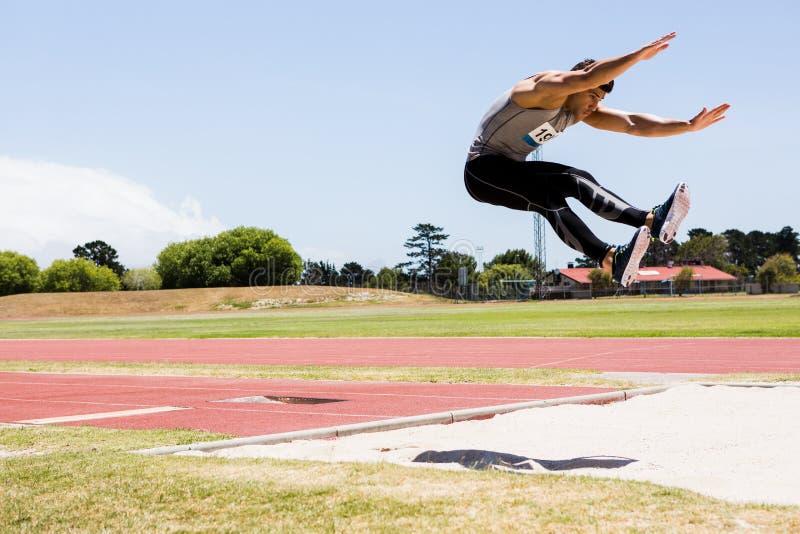 Atleta che esegue un salto in lungo fotografia stock libera da diritti