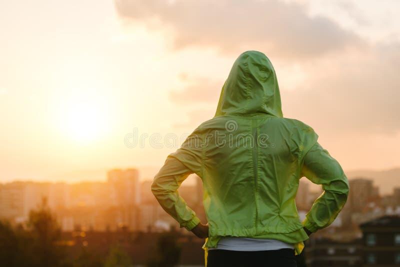 Atleta che guarda tramonto sopra l'orizzonte della città dopo l'esercitazione immagini stock
