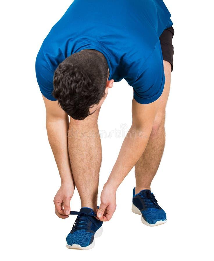 Atleta che lega i suoi laccetti isolati sopra fondo bianco Sportivo che indossa i legami neri e blu degli abiti sportivi le sue s immagini stock
