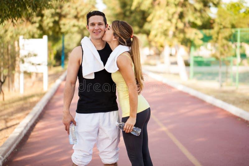 Atleta che ottiene un bacio dalla sua amica immagine stock