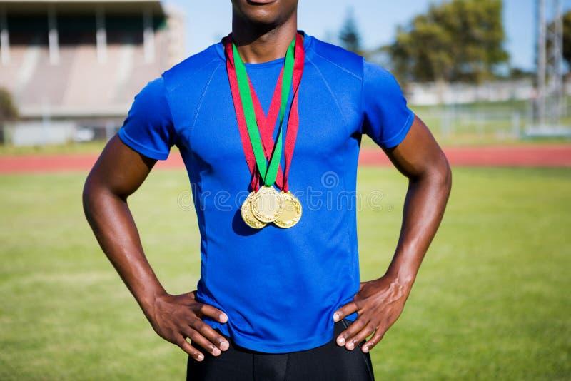 Atleta che posa con le medaglie d'oro dopo la vittoria fotografia stock