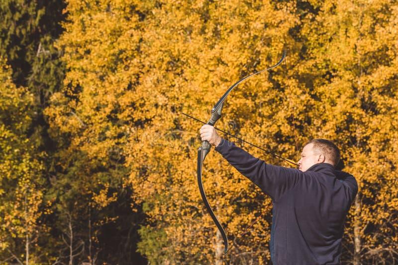 Atleta che punta su un obiettivo e sui tiri una freccia archery immagini stock libere da diritti