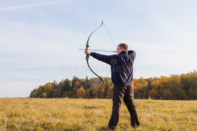 Atleta che punta su un obiettivo e sui tiri una freccia archery fotografie stock libere da diritti