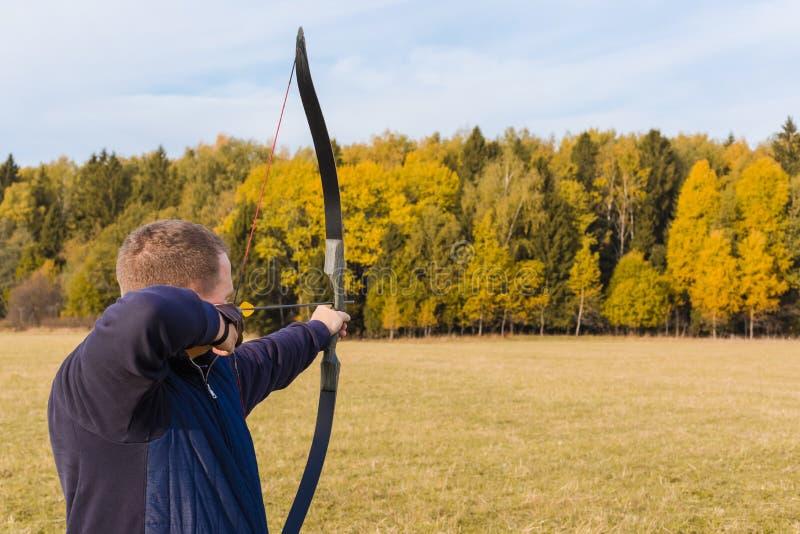 Atleta che punta su un obiettivo e sui tiri una freccia archery fotografia stock libera da diritti