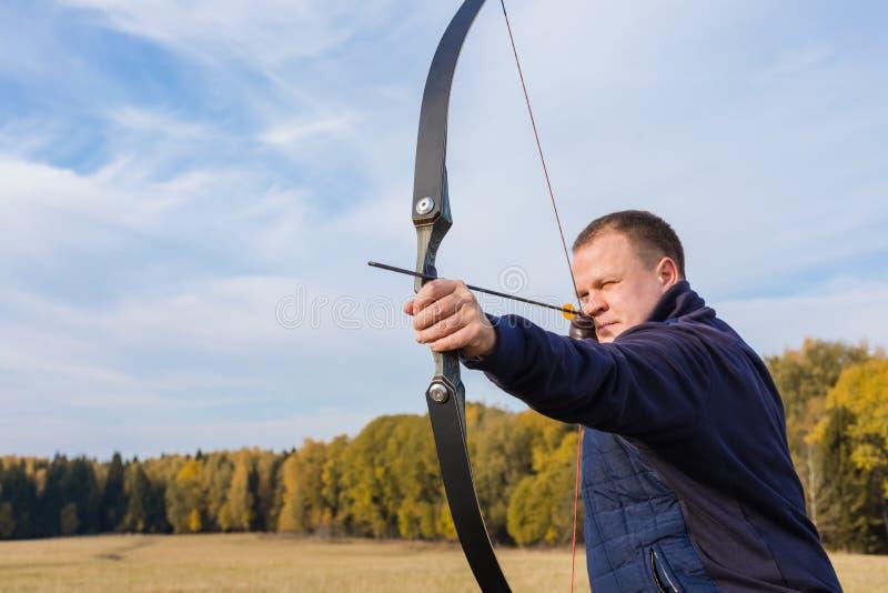 Atleta che punta su un obiettivo e sui tiri una freccia archery fotografia stock