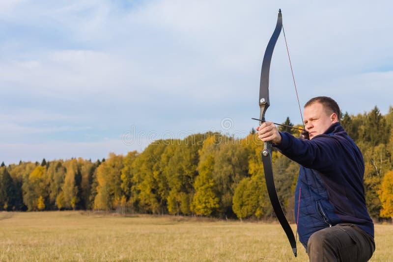 Atleta che punta su un obiettivo e sui tiri una freccia archery immagine stock