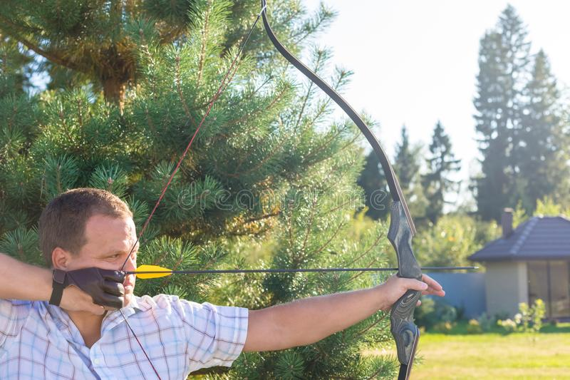 Atleta che punta su un obiettivo e sui tiri una freccia archery bandiera fotografia stock