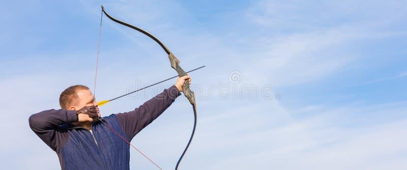 Atleta che punta su un obiettivo e sui tiri una freccia archery bandiera fotografie stock
