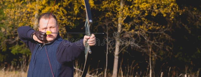 Atleta che punta su un obiettivo e sui tiri una freccia archery bandiera immagine stock