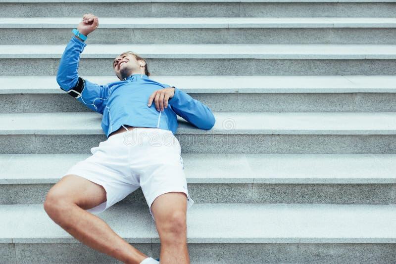 Atleta che riposa sulle scale dopo avere corso, sul bracciale con il telefono e sulle cuffie con musica per prepararsi fotografia stock libera da diritti