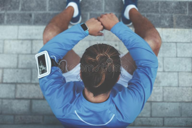 Atleta che si siede sulla via dopo la sessione ed il riposo di allenamento, sul bracciale con il telefono cellulare, sulle cuffie immagini stock libere da diritti