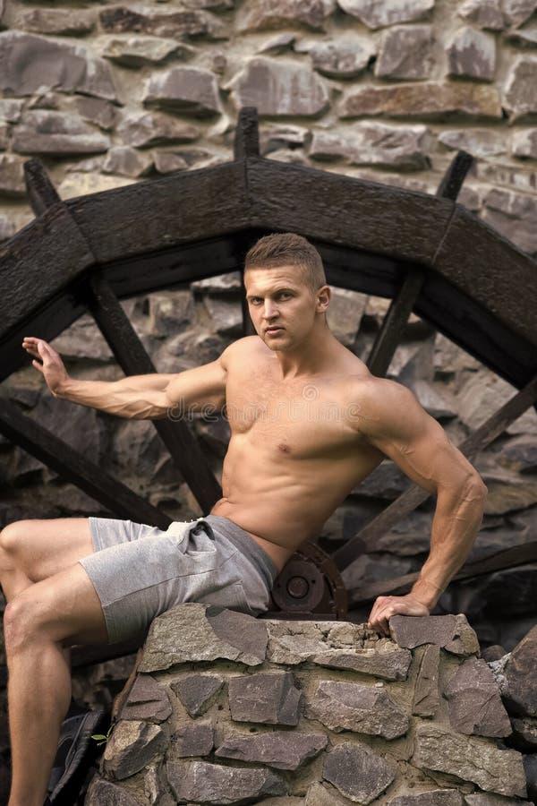 Atleta com seis blocos, ab, bíceps, tríceps no short imagens de stock