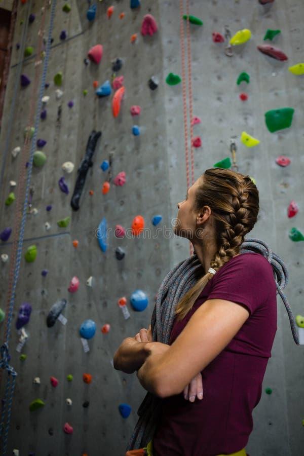 Atleta con la cuerda que mira para arriba mientras que hace una pausa la pared que sube en club fotos de archivo libres de regalías