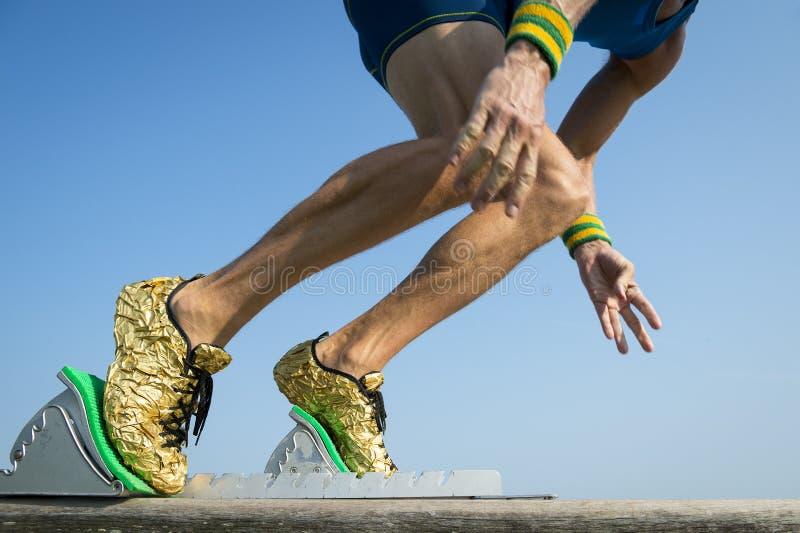 Atleta con las zapatillas deportivas del oro que comienzan una raza foto de archivo