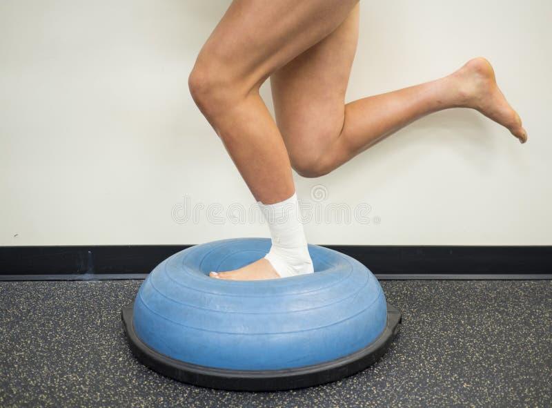 Atleta con un tobillo torcido que hace ejercicios de la consolidación y de la balanza en una bola del bosu fotografía de archivo libre de regalías
