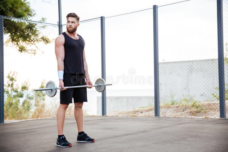 Atleta concentrado do homem novo que dá certo com barbell foto de stock royalty free