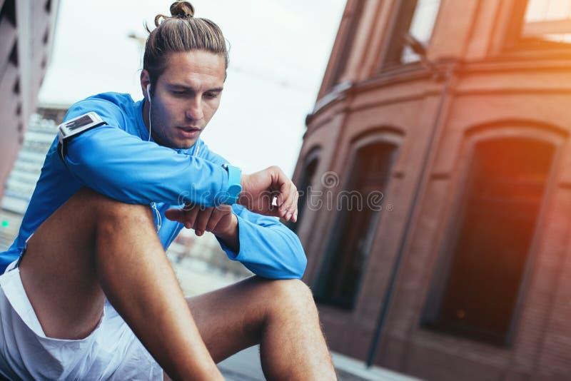 Atleta considerável que verifica resultados do exercício com seu relógio esperto, sentando-se na rua e descansando após movimenta fotografia de stock