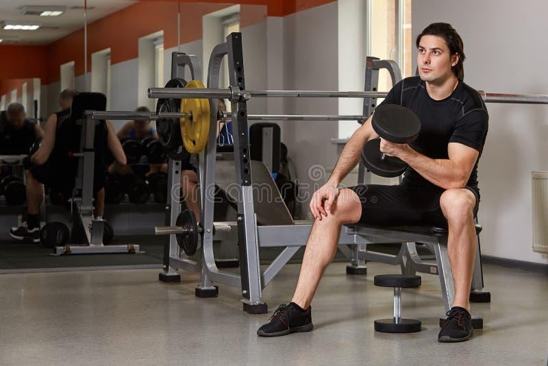 Atleta construido muscular joven que se resuelve en un gimnasio, sentándose en una máquina del levantamiento de pesas y las pesas imagen de archivo libre de regalías