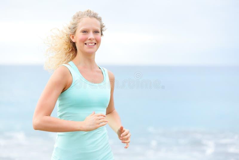 Atleta corrente della donna che pareggia fuori sulla spiaggia fotografia stock libera da diritti