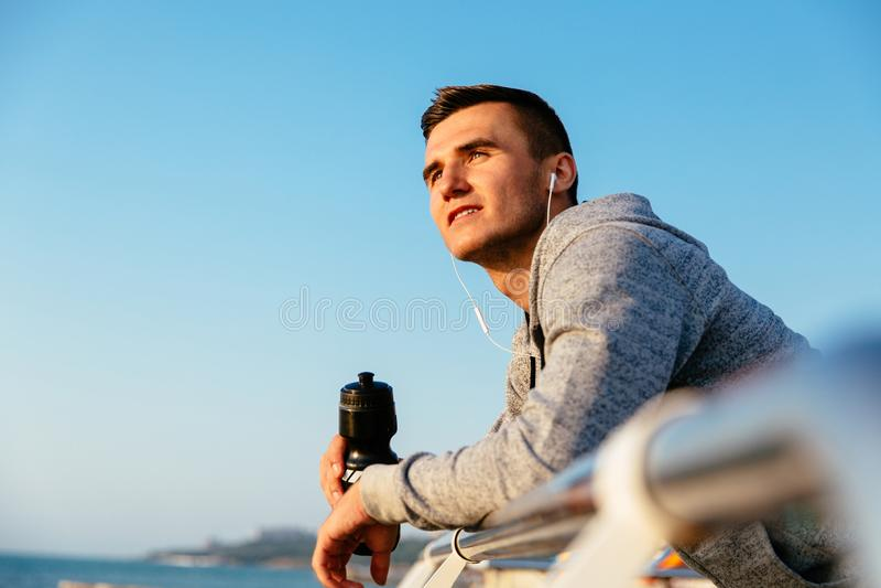 Atleta cuidadoso no cais, com garrafa de água foto de stock royalty free