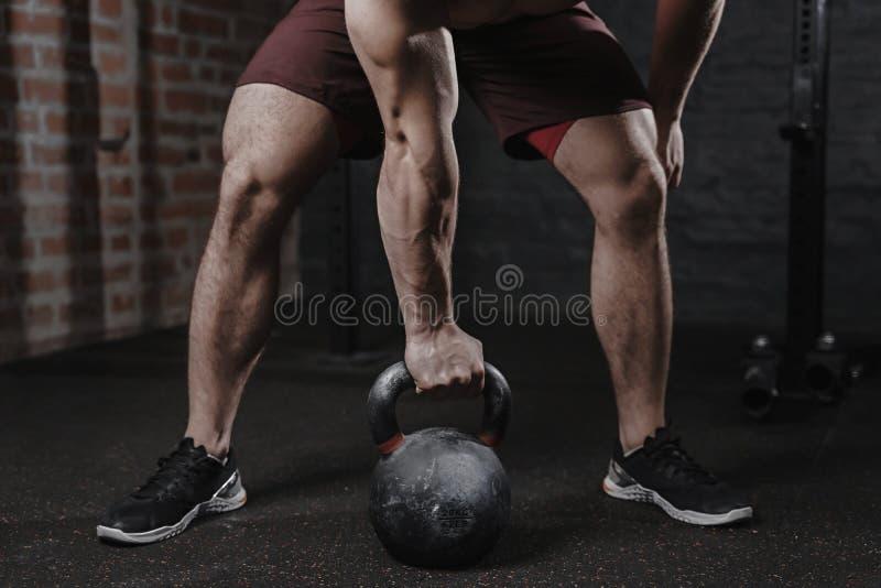Atleta de Crossfit que ejercita con el kettlebell en el gimnasio Hombre hermoso que hace el entrenamiento funcional Entrenamiento imagen de archivo libre de regalías