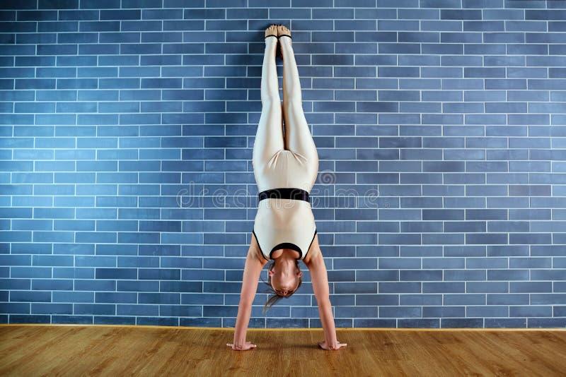 Atleta de la muchacha en headstand cerca de la pared de ladrillo el gimnasio El hacer de la mujer imagenes de archivo