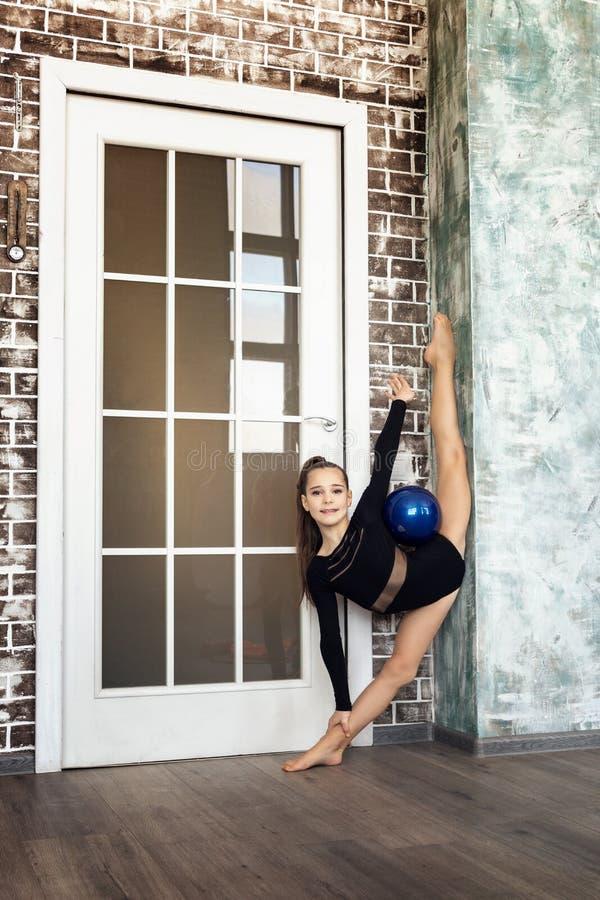 Atleta de la muchacha que hace la gimnasia del ejercicio, haciendo un ejercicio con una espada azul en una secuencia vertical fotografía de archivo libre de regalías