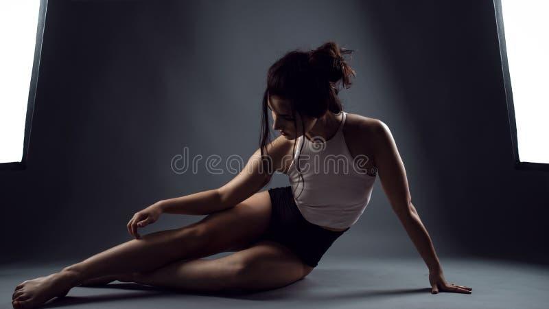 Atleta de la mujer en bragas negras de la cintura alta y el top del blanco que se sientan en el piso y que tocan su pierna fotos de archivo