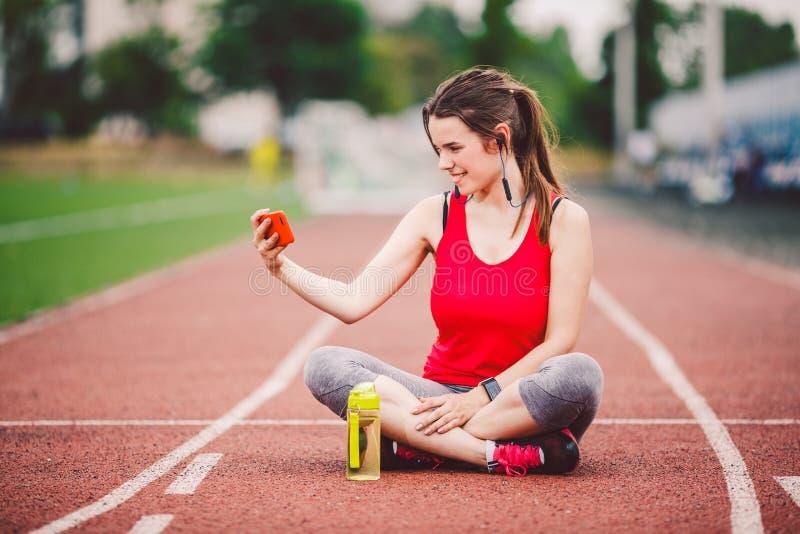Atleta de la mujer joven en la forma de vida que se divierte del estadio, sentándose en la pista, tomando la foto del selfie en u fotos de archivo libres de regalías