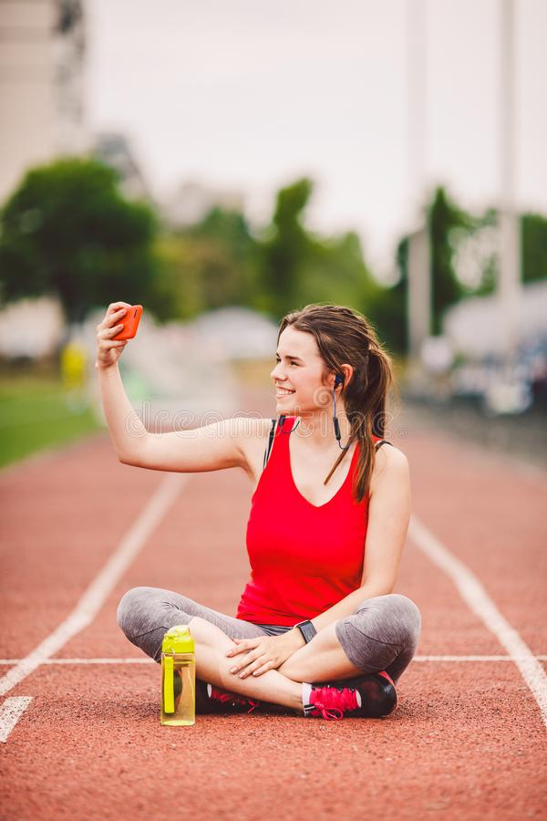 Atleta de la mujer joven en la forma de vida que se divierte del estadio, sentándose en la pista, tomando la foto del selfie en u imagen de archivo