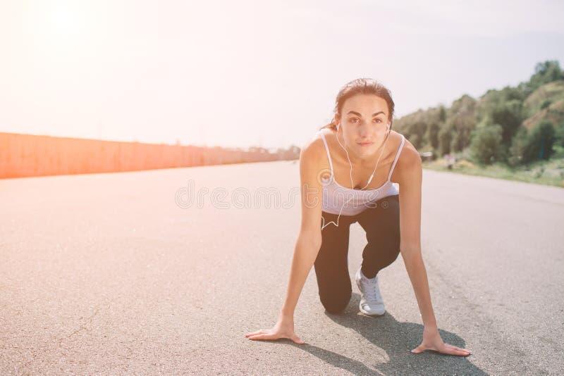 Atleta de la mujer joven en la posición de salida lista para comenzar una raza El esprinter de sexo femenino listo para los depor fotografía de archivo