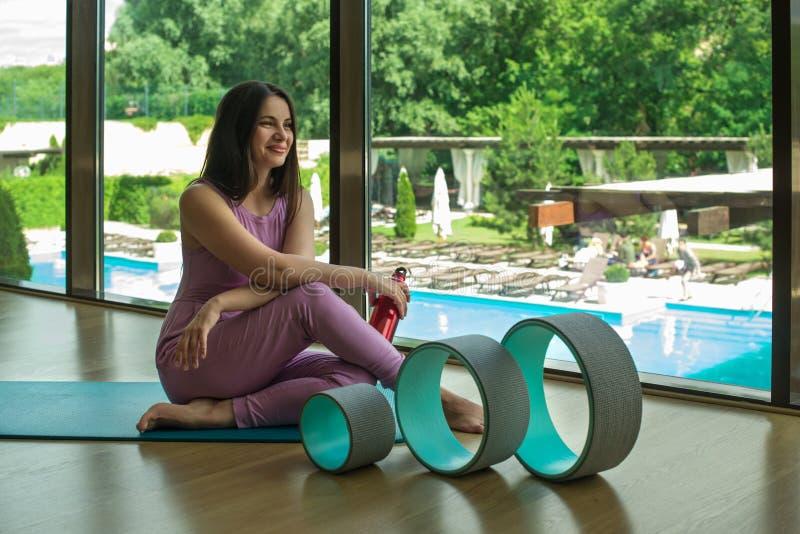 Atleta de la mujer joven que descansa después de ejercicios con los anillos para la yoga foto de archivo libre de regalías
