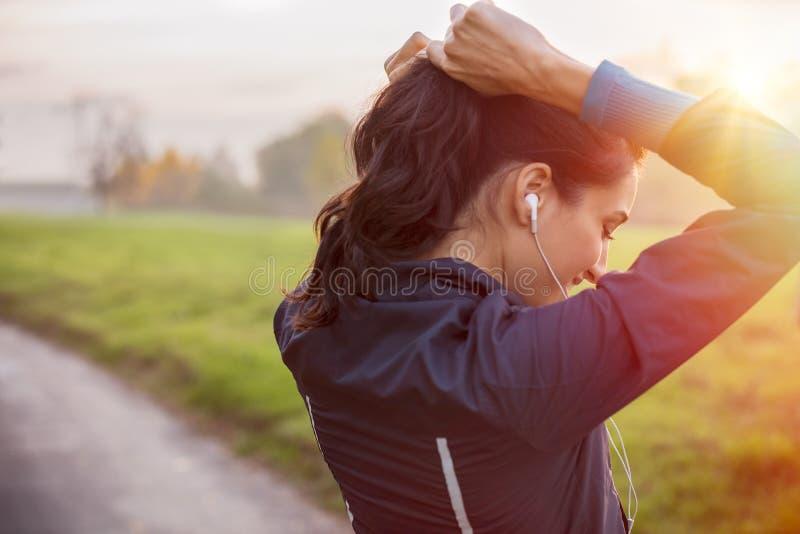 Atleta de la mujer que ata el pelo foto de archivo libre de regalías