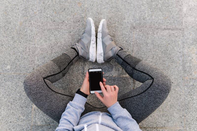 Atleta de la mujer que usa el entrenamiento de funcionamiento de la actividad elegante del teléfono imagenes de archivo