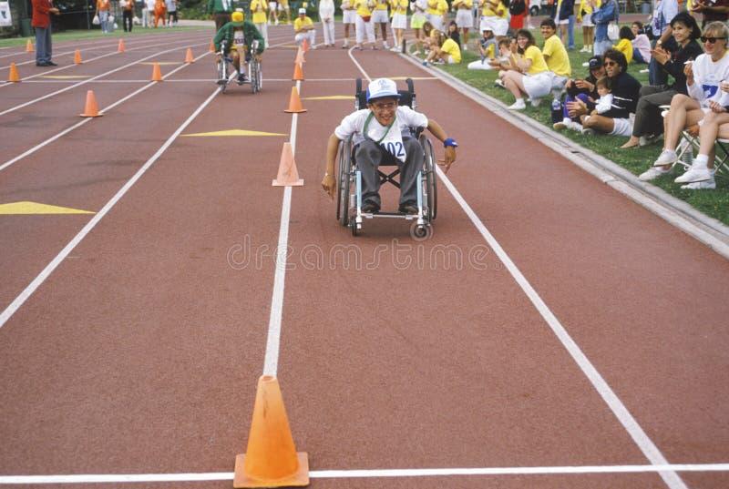 Atleta de las Olimpiadas especiales de la silla de ruedas que compite en la raza, meta inminente, UCLA, CA imágenes de archivo libres de regalías