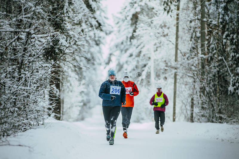 Atleta de meia idade da mulher que corre abaixo do parque da aleia na neve o tempo está frio imagens de stock royalty free