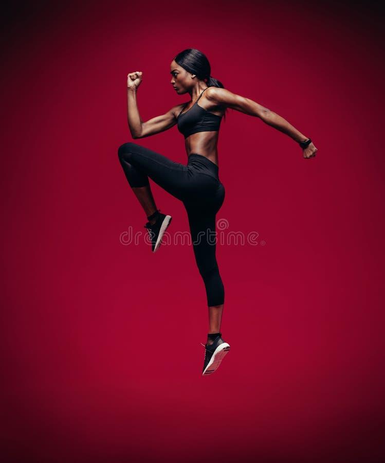 Atleta de sexo femenino africano que salta y que estira imágenes de archivo libres de regalías