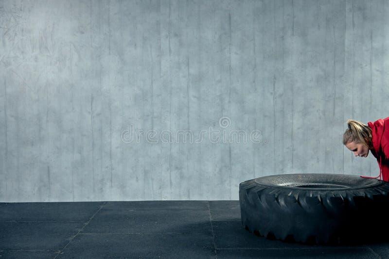 Atleta de sexo femenino apto que se resuelve con un neumático enorme, dando vuelta y moviendo de un tirón en el gimnasio fotos de archivo